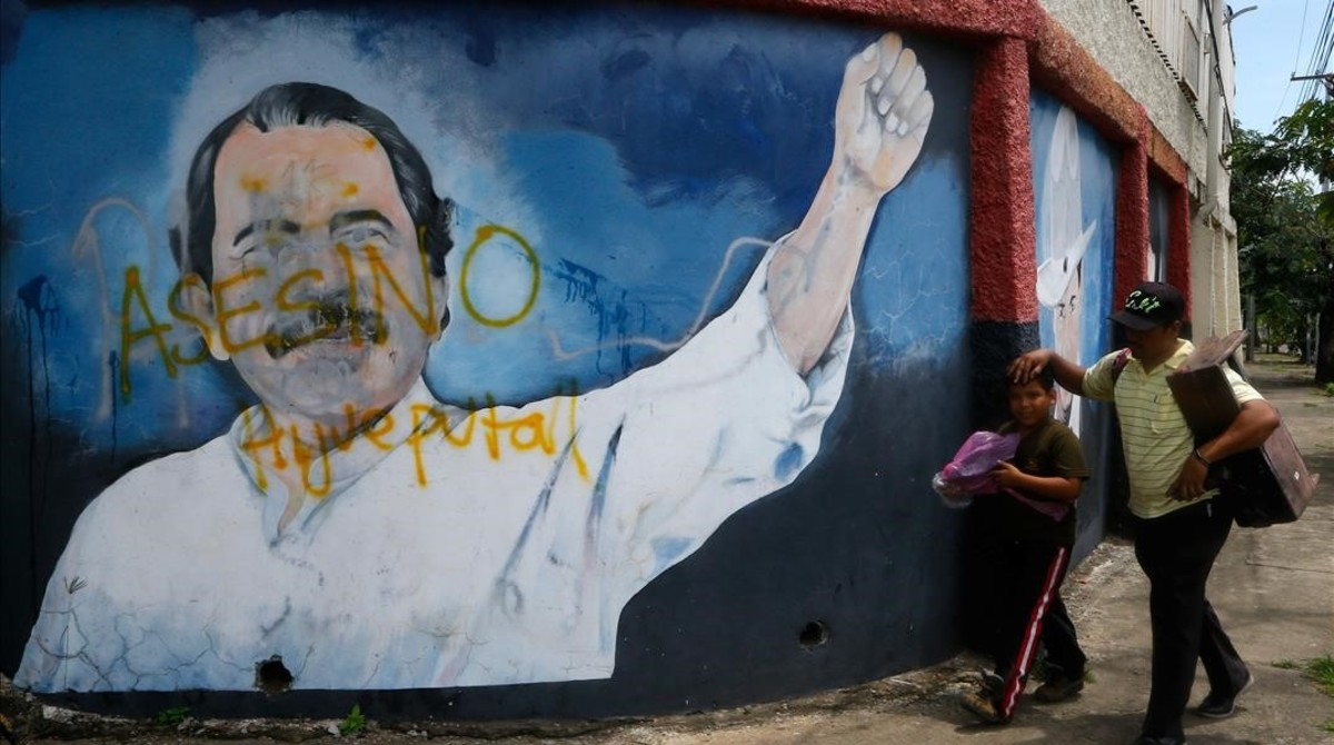 Dos personas pasan junto a un mural de Daniel Ortega en Managua.