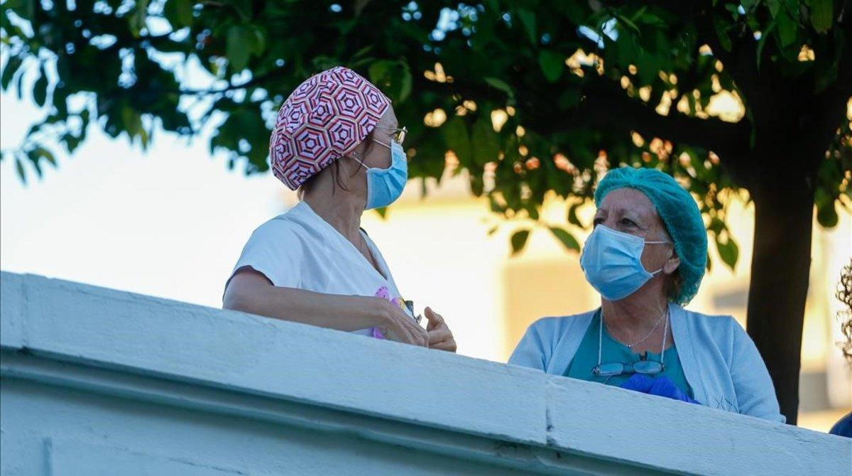 Dos sanitarias en el patio del Hospital Virgen del Rocío de Sevillacon mascarillas.