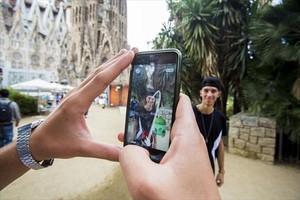 Dos usuarios de Pokémon Go frente a la Sagrada Família.