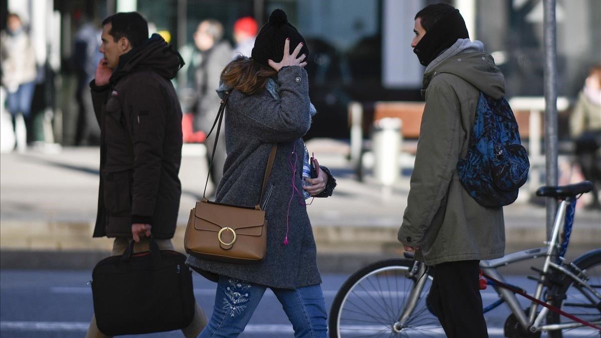 Ciudadanos de Barcelona se protegen del frío, este viernes por la mañana.