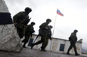 Un grup de soldats armats caminen a prop dun accés a la base militar situada a la localitat de Perevalnoie, als voltants de Simferópol, a la península ucraïnesa de Crimea, el passat dia 7.