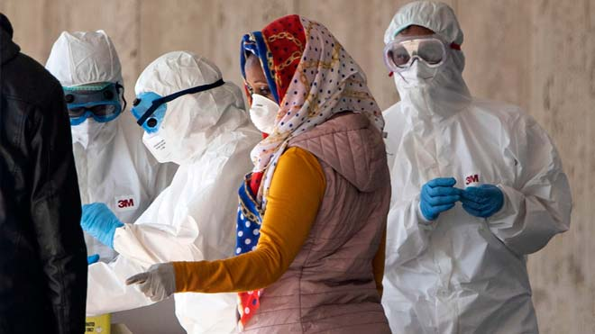 Italia constata el mayor frenazo en los contagios de coronavirus en 25 días. En la foto, unos sanitarios recogen muestras de habitantes de un edificio en Roma.
