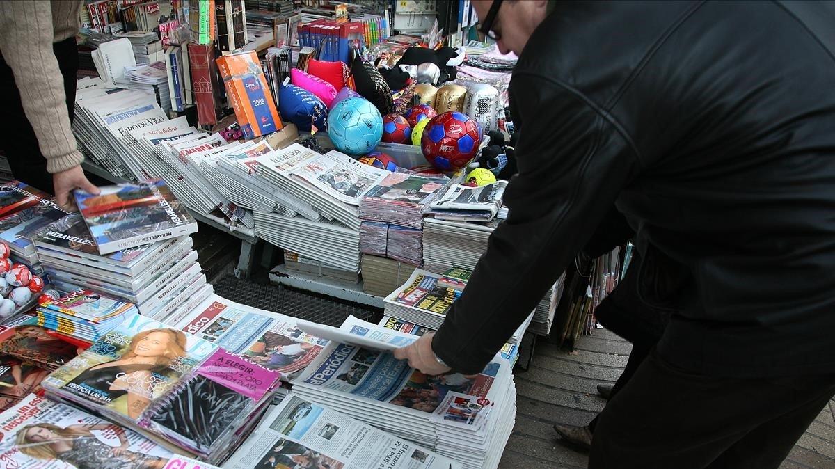 Un hombre compra un periódico en un quiosco de Barcelona.