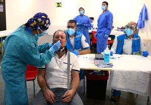A man has a swab sample taken for a coronavirus disease (COVID-19) antigen test at a cultural centre in the working class neighbourhood of Vallecas in Madrid, Spain October 1, 2020. REUTERS/Sergio Perez