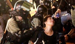 Oficiales de la policía antidisturbios vierten agua sobre un manifestante durante su detención en Hong Kong.