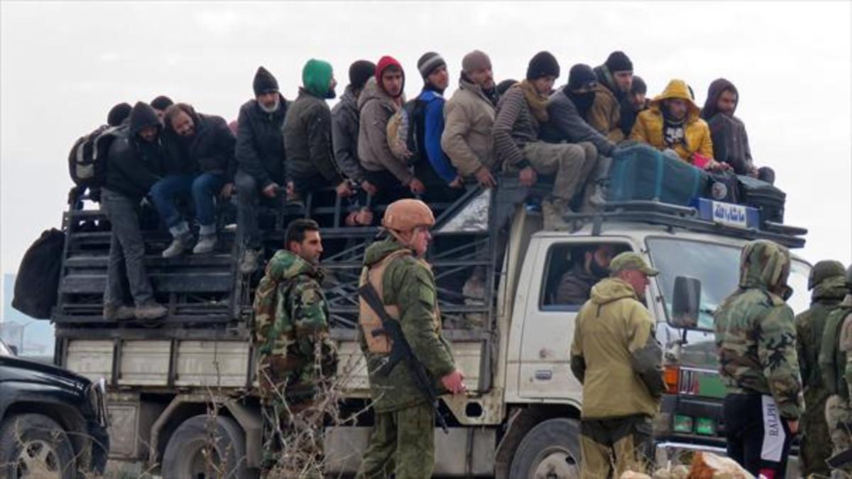 Salida de civiles y combatientes rebeldes Alepo bajo la estrecha vigilancia de soldados rusos y de las fuerzas progubernamentales esta semana.