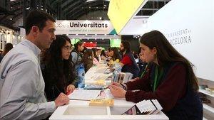 Asistentes al Saló de l'Ensenyament piden información en el estand de la Universitat de Barcelona.
