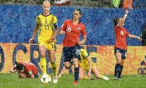 La jugadora sueca Stina Blackstenius y la chilena Daniela Zamora, bajo la lluvia, durante el Mundial 2019, en Rennes.