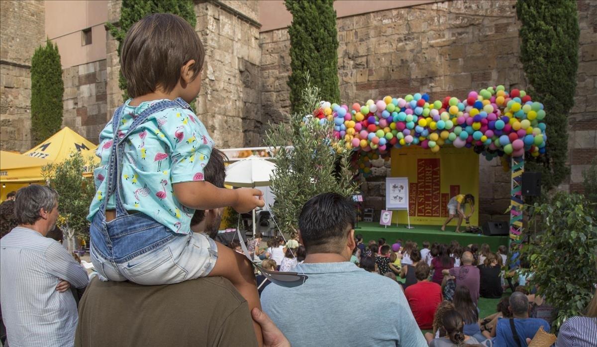 Padres e hijos disfrutan de la Setmana del Llibre en Català, en la Avenida de la Catedral.
