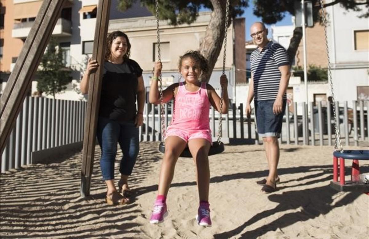 Erika Valero, jugando en unparque de Badalona, con sus padres.