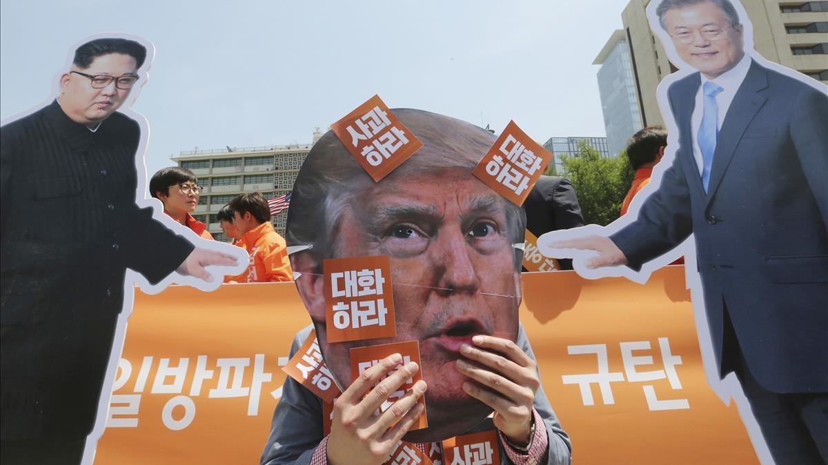 Un manifestantes se cubre la cara con una máscara deDonald Trump junto a una foto del líder norcoreano,Kim Jong Un, y el presidente de Corea del Sur,Moon Jae-in (derecha).