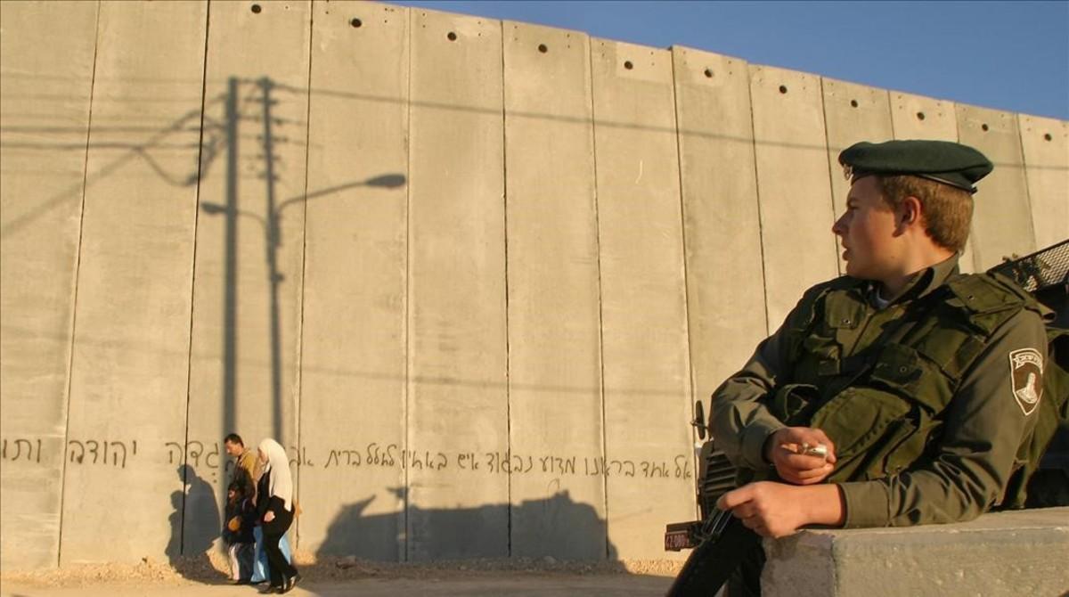 Una familia palestina camina frente a un policía de fronteras israelí, junto al muro que divide en dos la localidad cisjordana de Abu Dis, el 9 de febrero del 2004.