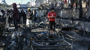 Unos migrantes permanecen junto a uno de los contenedores quemados en el incendio declarado en el campo de refugiados de Moria, en el que murió una niña.