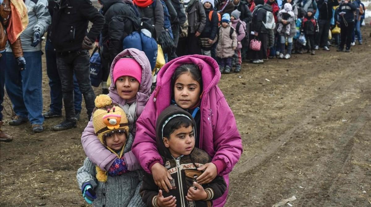 Unos niños sirios esperan junto a otros refugiados para cruzar la frontera entre Macedonia y Serbia.