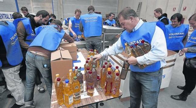 Unos voluntarios clasifican los productos recogidos durante la campaña del Gran Recapte del Banc dels Aliments.