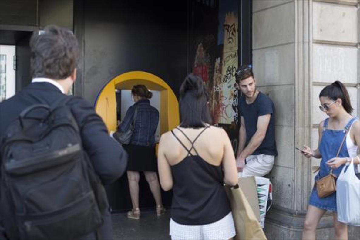 Varias personas esperan para operar en un cajero de una oficina de CaixaBank en la plaza de Catalunya.