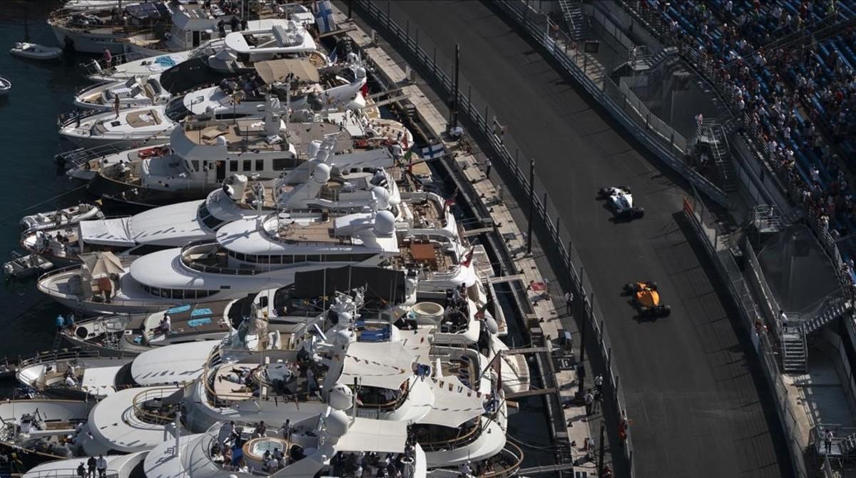 El Williams de Sirotkin y el McLaren de Vandoorne pasan frente a los yates del puerto deportivo de Mónaco.