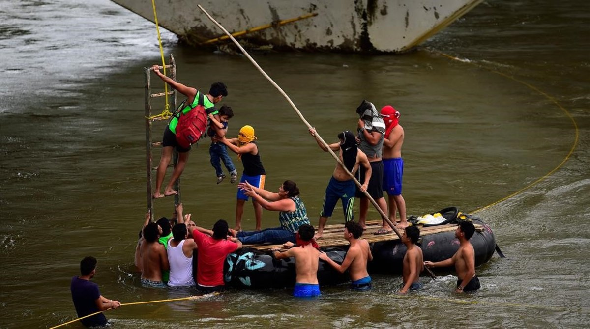 Inmigrantes hondureños socorren a un hombre y un niño en el río Suchiate, en el puente fronterizo de Ciudad Hidalgo, entre Guatemala y México, el 20 de octubre del 2018.