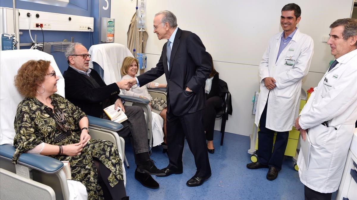 El presidente de la Fundación Bancaria La Caixa, Isidro Fainé, saluda a pacientes en el Hospital Clinic de Barcelona.