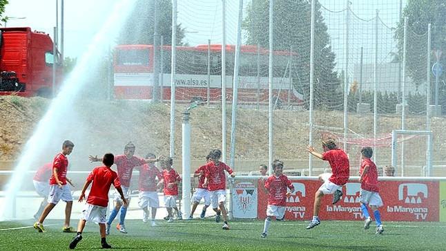 Un grupo de niños futbolistas del Atletic Segre de Lleida juega bajo las regaderas del campo.