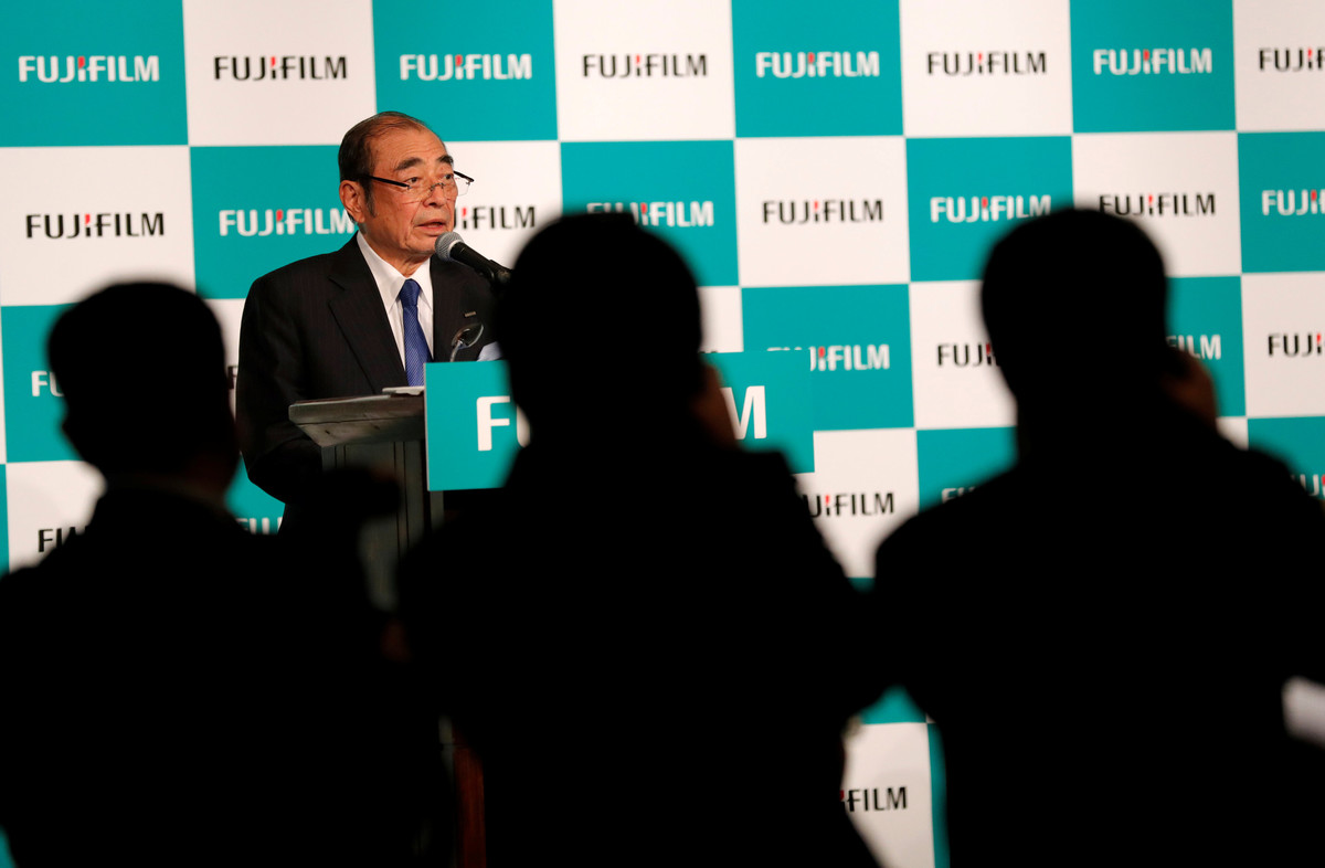 Photographers take pictures of Fujifilm Holdings Chief Executive Officer Shigetaka Komori who is speaking at a news conference in Tokyo