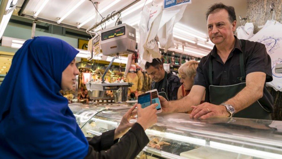 Una clienta paga con recs en un mercado.
