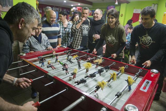 Manuel Soto, propietario del bar El Jardí, juega con el equipo moreno contra Ignasi de la Fuente y Mónica García, rodeados de miembros de Los Heavys de la Meri.
