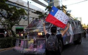 Un joven protesta enfrente de un vehículo militar en Chile.