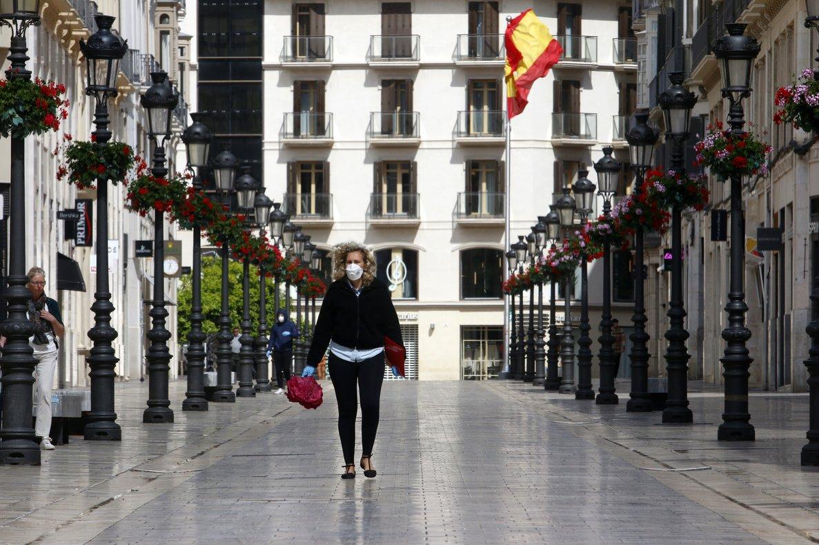 Una mujer con mascarilla por el coronavirus, en la calle Larios de Málaga.