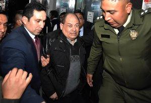 AME1899. LA PAZ (BOLIVIA), 14/01/2020.- El exministro boliviano Carlos Romero (c), que tuvo un gran peso en el Gobierno de Evo Morales, ingresa este martes a la Fiscalía con custodia policial para declarar dentro de un caso de supuesta corrupción, tras salir de un hospital desde el que denunció que es acosado por motivos políticos, en La Paz (Bolivia). Canales de televisión mostraron el momento en que Romero, que hasta noviembre pasado fue ministro de Gobierno (Interior), abandonaba la clínica en la que estuvo ingresado desde el fin de semana para abordar un vehículo que le trasladó hasta las oficinas del Ministerio Público en La Paz. El abogado de Romero, Andrés Zúñiga, explicó a los medios que el documento presentado para el traslado de la exautoridad a la Fiscalía no menciona la palabra aprehensión, sino que es una orden de conducción para llevarlo para que declare ante el Ministerio Público. EFE/ Stringer
