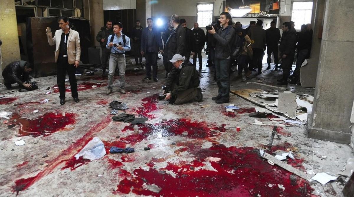 Fotografia facilitada por la agencia SANA que muestra a varios periodistas inspeccionando el lugar del atentado suicida.