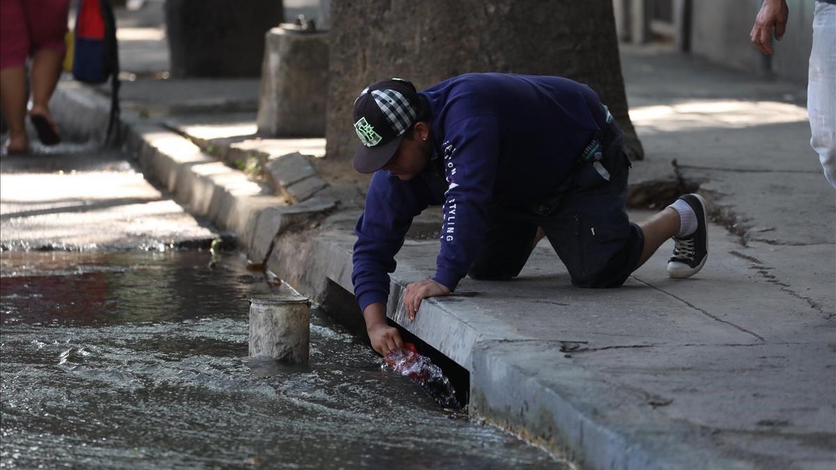Decenas de caraqueños decidieron recoger agua del alcantarillado de la ciudad y del contaminado rio Guaire debido a la imposibilidad de recibir agua en los hogares por causa del apagon que afecta al pais desde el pasado jueves.