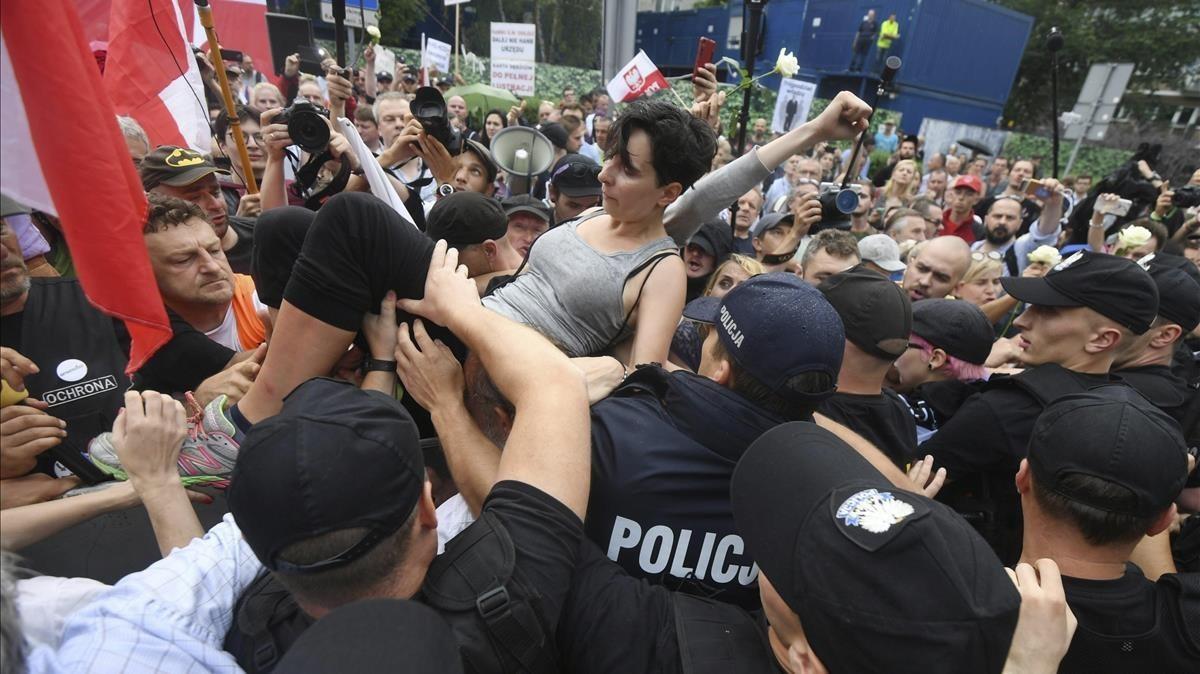 Un grupo de personas intentan romper la barrera formada por la policia durante una protesta en Polonia.