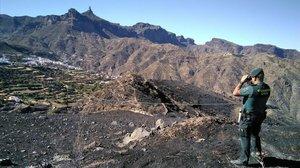 Un guardia civil observa parte de la superficie quemada por el fuego en Gran Canaria.