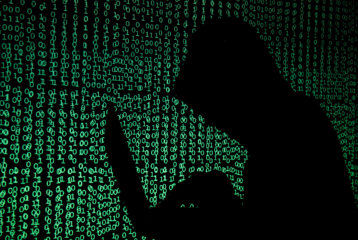 A hooded man holds a laptop computer as cyber code is projected on him in this illustration picture taken on May 13, 2017. Capitalizing on spying tools believed to have been developed by the U.S. National Security Agency, hackers staged a cyber assault with a self-spreading malware that has infected tens of thousands of computers in nearly 100 countries. REUTERS/Kacper Pempel/Illustration