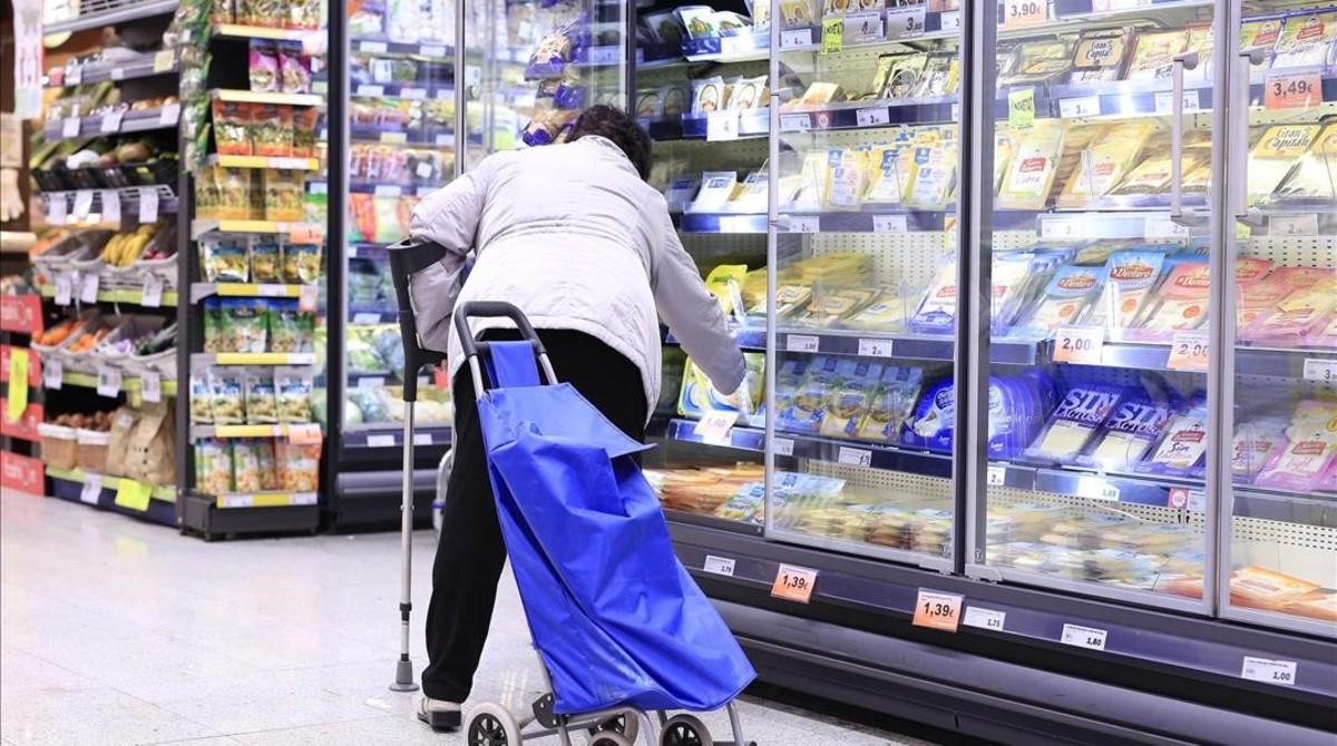 Una mujer en la sección de productos congelados de un supermercado.
