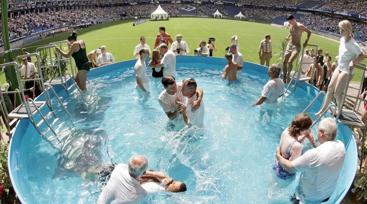 Asistentes al congreso especial de los Testigos de Jehováson bautizados durante una ceremonia múltiple.