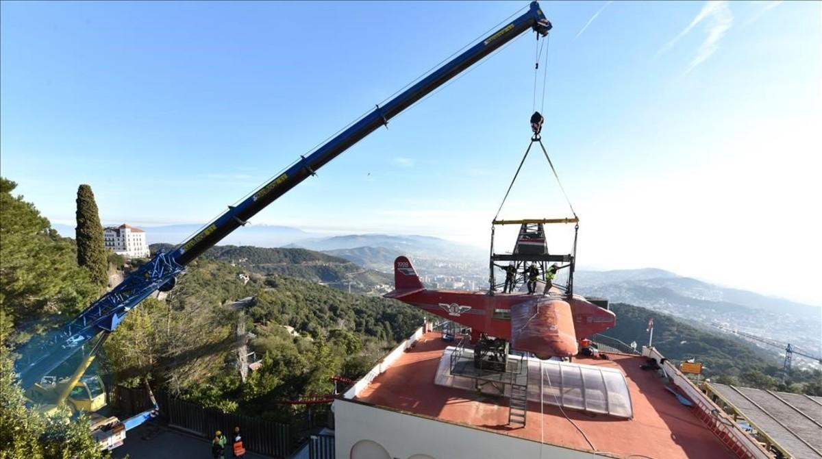 Un grúa descuelga el avión del Tibidabo para ser restaurado.