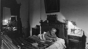 Josep Pla, rodeado de libros y liándose un pitillo, en la cama de la habitación de su madre, en la masía de Llofriu, donde murió en abril de 1981.
