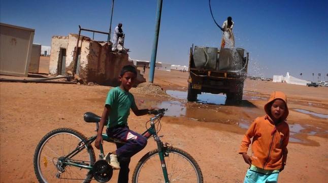 Jóvenes saharauis junto a una cisterna que reparte agua a precario en el campamento Dajla (Tinduf), en una imagen de archivo.
