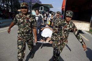 Soldados portan a un paciente de vuelta al hospital.