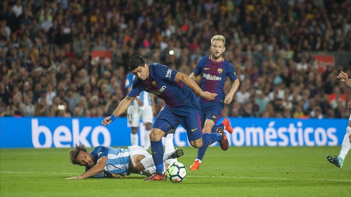 Luis Suárez se escapa de Baysse, el jugador del Málaga, en el Camp Nou.