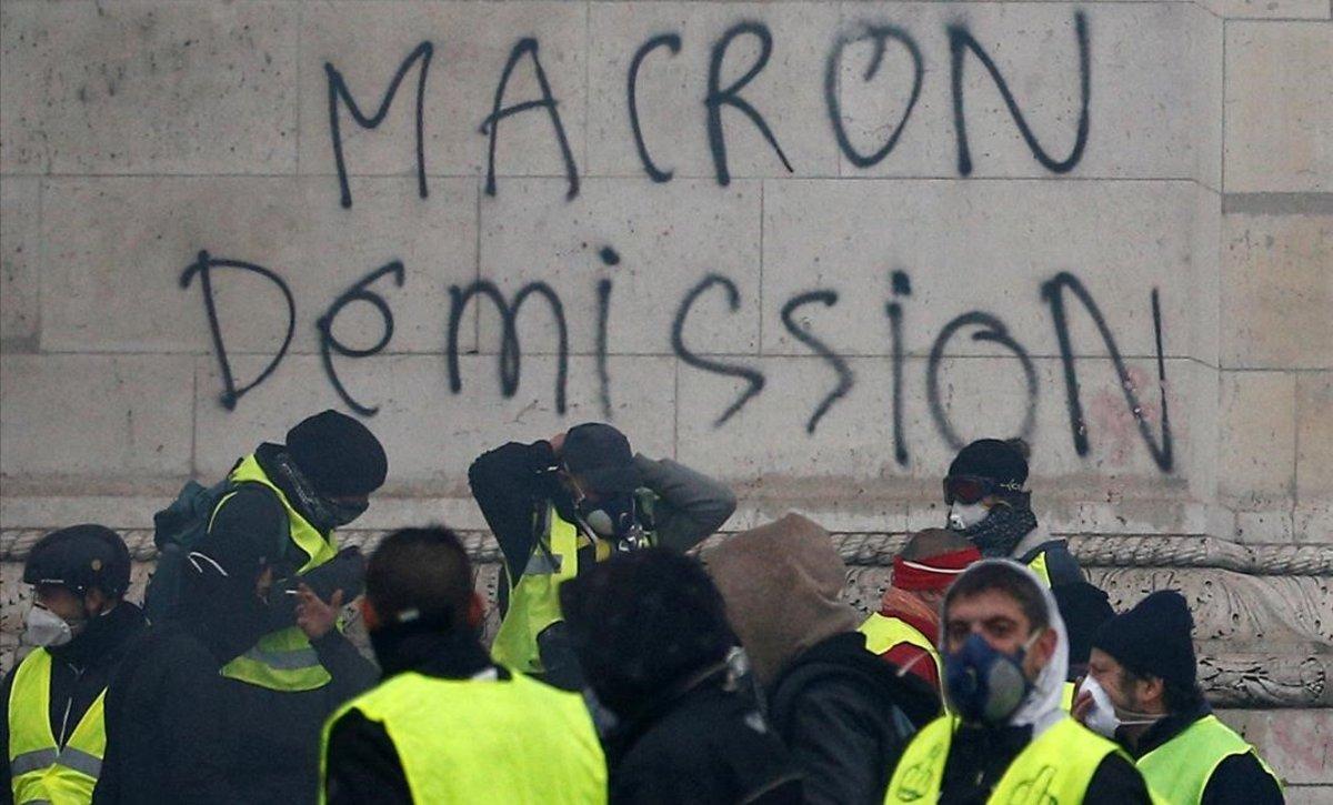 Manifestantes de los chalecos amarillos ante una pintada que pide la dimisión de Macron, en París.