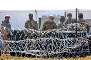 Military personnel stand behind bared wire as U S  Secretary of Defense James Mattis visits Base Camp Donna in Donna  Texas.   Joel Martinez The Monitor via AP