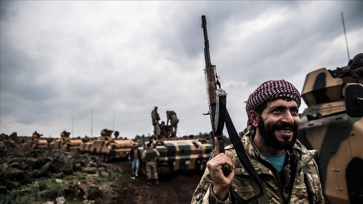 Un soldado turco frente a una columna detanques en la frontera con Siria.