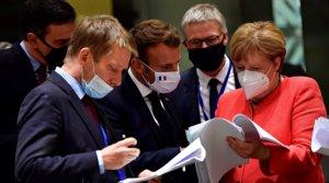 Pedro Sánchez (izquierda), Emmanuel Macron (centro) y Angela Merkel (derechan) examinan los documentos del acuerdo sobre el fonde de reconstrucción, el 20 dejulio del 2020 en Bruselas.