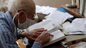 Petr Brandejsky, un superviviente del Holocausto de 90 años, lee un libro en su vivienda durante el confinamiento, en Praga el 24 de abril.