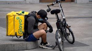 Un repartidor de Glovo revisa sus mensajes en el móvil en una plaza de Madrid, el pasado 30 de abril, en plena pandemia.