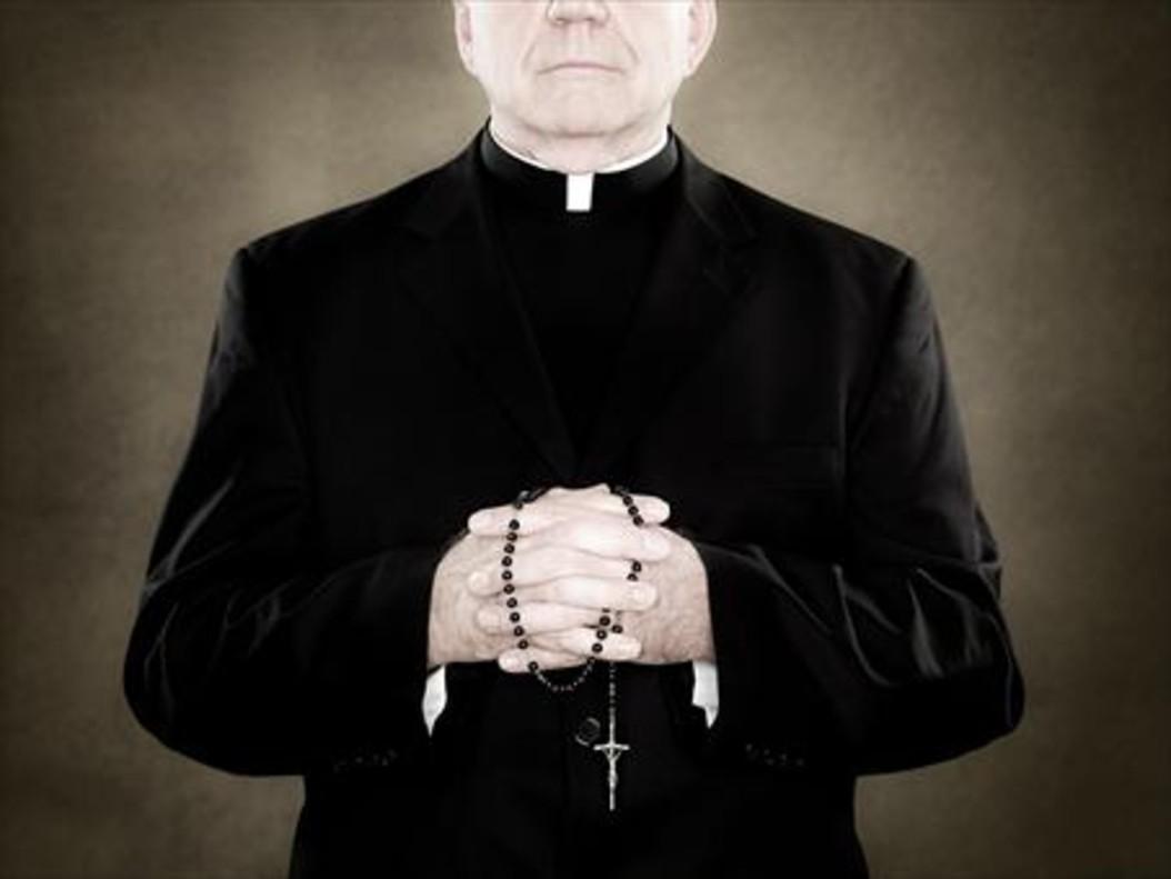 Un sacerdote sujeta un rosario.