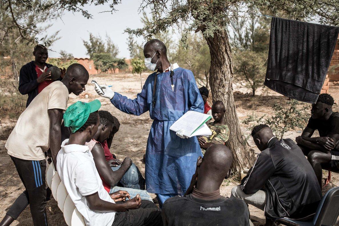 Un sanitario toma la temperaturas a jóvenes en Dakar, Senegal.